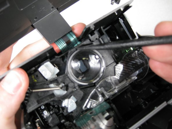 Carefully use spudger to release lens, then lift lens out of camera with fingers.