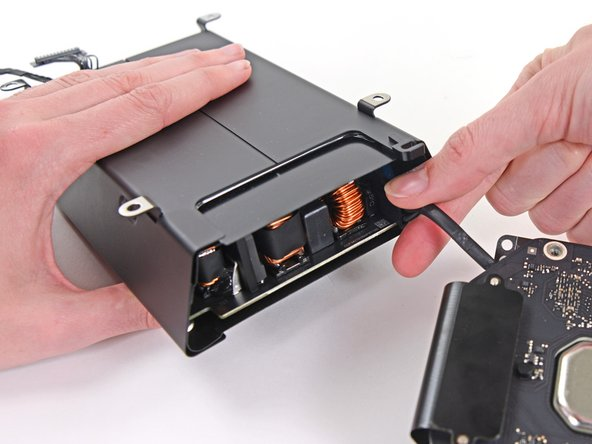 Squeeze the AC power inlet cable connector and pull it straight out of its socket in the power supply.