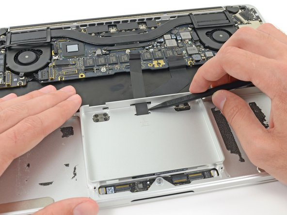 Insert the tip of a spudger in between the trackpad ribbon cable and the upper case inside the SSD assembly cavity to remove the last of the adhesive.