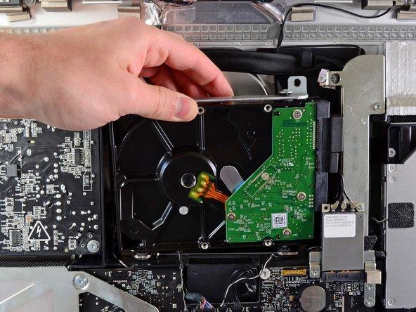 Ruotare leggermente il disco rigido dal case esterno e sollevarlo dai piedini di montaggio verso il bordo superiore dell'iMac.