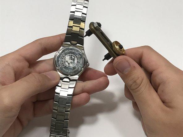 Usando una chiave inglese regolabile, svita la facciata posteriore dell'orologio.