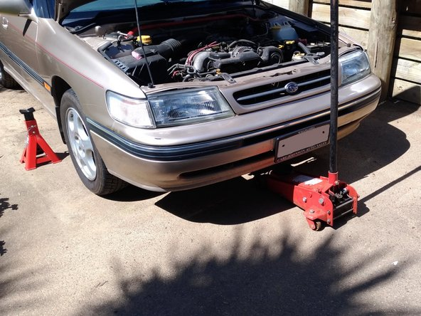 Jack up the front of the car from the centre jack point if you have a hydraulic jack
