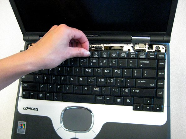Lift the back edge of the keyboard and pull towards the screen.
