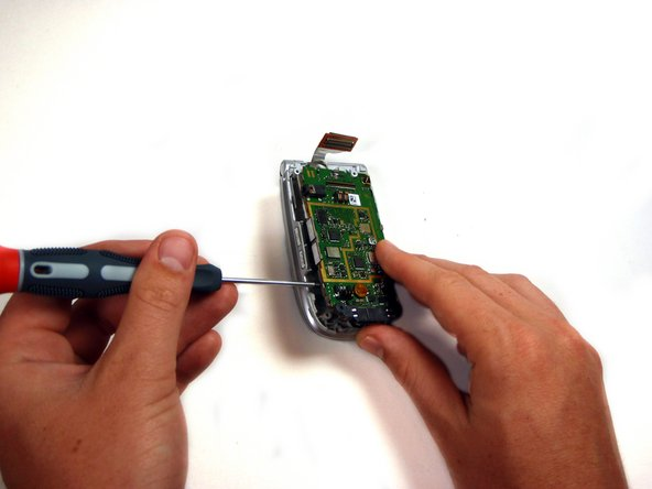 Use a flathead screwdriver to gently pry the logic board and keypad from the device.
