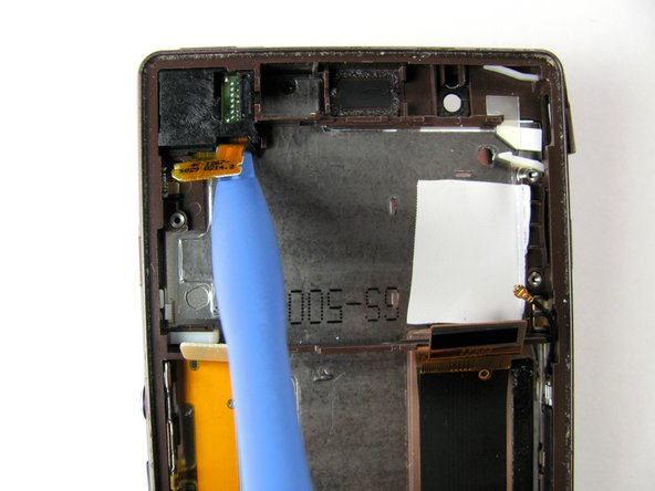 Place the plastic opening tool under the bottom side of the orange pop connector, and lift up towards the center of the headphone jack. The pop connector is located at the top left of the phone.