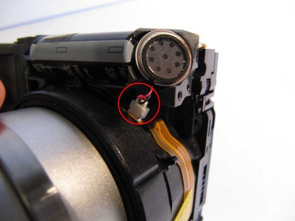 On the bottom left hand side of the lens assembly there is a connector with a red and a black wire going to the speaker. Disconnect this, taking great care not to strain the wires or especially the ribbon that the socket is mounted on.