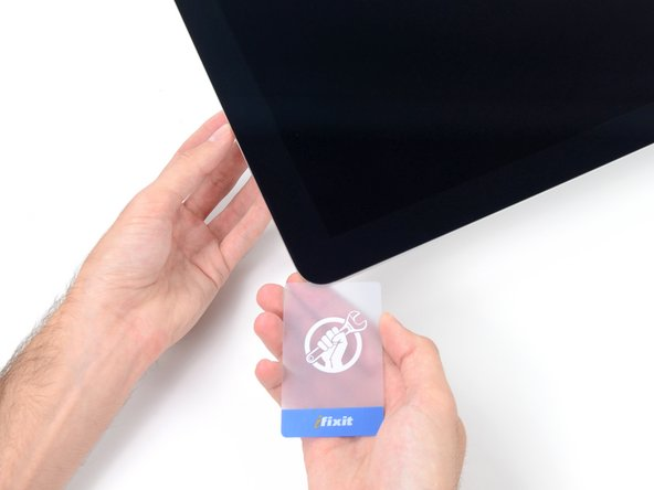 While the opening tool cut most of the adhesive, the display will still be slightly adhered to the case. A plastic card will be necessary to free up the last of this adhesive.