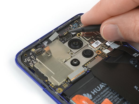 At first glance, the motherboard looks free to jump right out, but a closer look reveals nine flex cables holding it in place, plus an antenna cable.