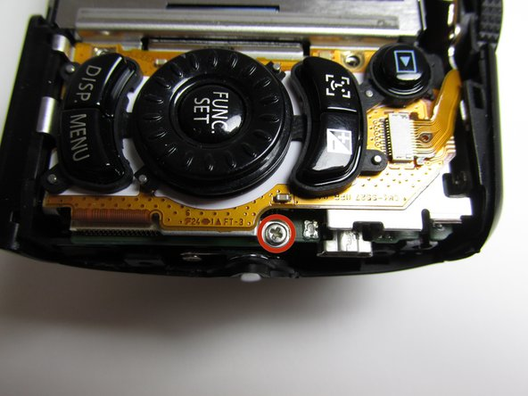 Place the camera with the lens facing down. Find the screw that is located on the right side of the camera next to the function set button.