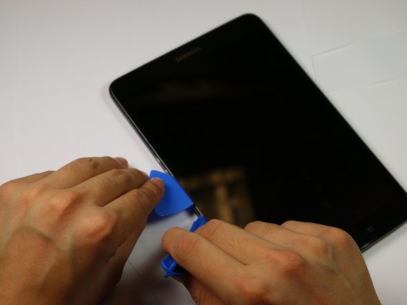 Insert the plastic opening tool into the gap between the screen and tablet in the location where you want to start removing the screen.