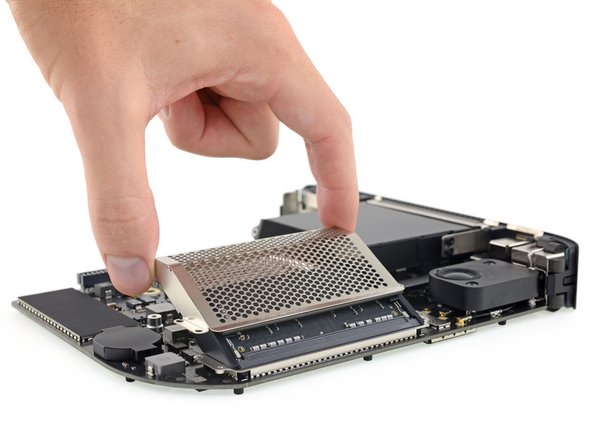 With the board out, we're going straight for the RAM. Apple has trapped it in a heavy metal cage—almost as if they don't fully trust modular RAM to behave itself.