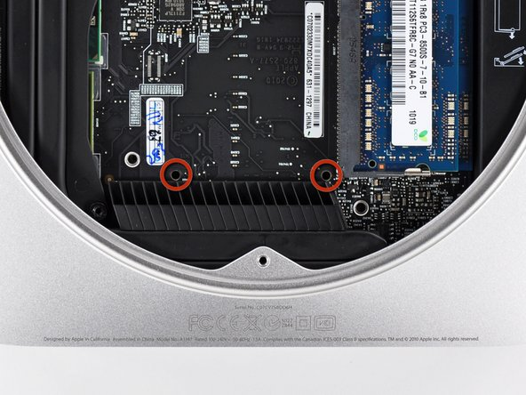 For enough clearance to remove the hard drive, the logic board must be slightly removed. To accomplish this, two cylindrical rods must be inserted into the holes highlighted in red.