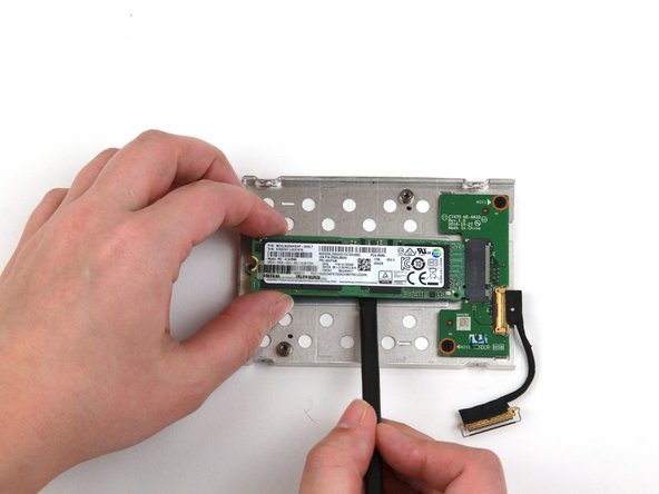 Use the flat end of a spudger to pry the SSD up slightly and pull it out of the slot with your other hand.