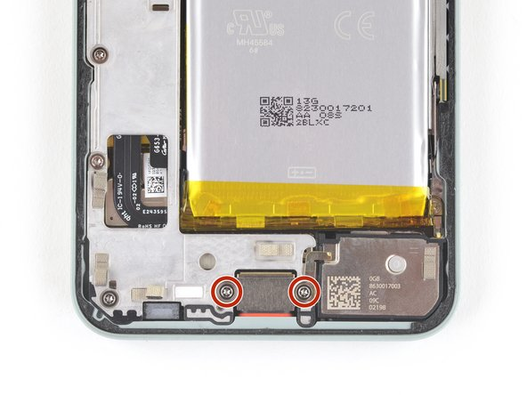 Use a T3 Torx driver to remove the two 4.6 mm-long screws securing the charging plate cover to the midframe.