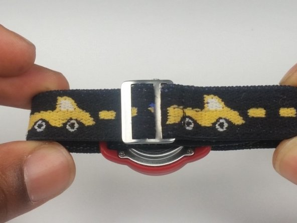 Pull on the watch strap  through the top of the strap buckle to unlock the strap.