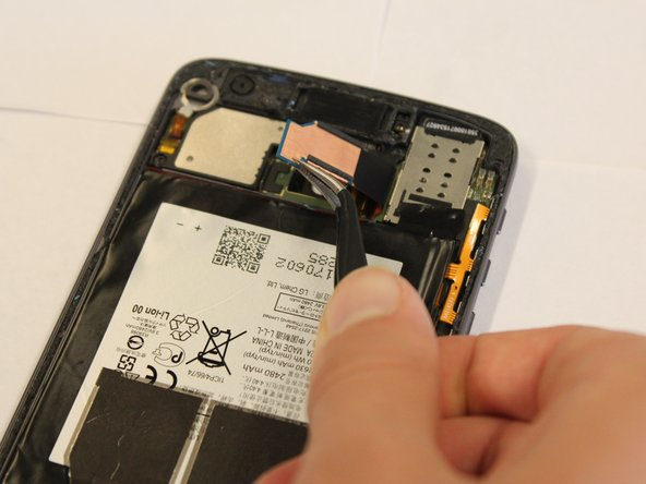 Slowly and carefully lift up on the tab until it pops out of the phone and is only connected by the black tape.