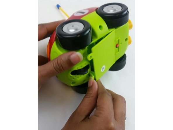 Pull up the tab to reveal the battery compartment.