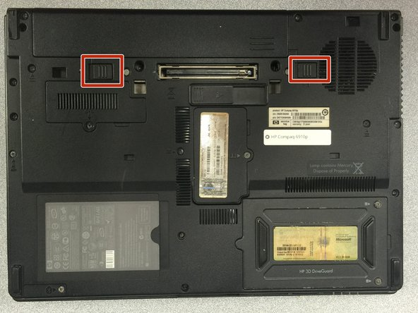 Flip the laptop upside down so the battery compartment is facing up.