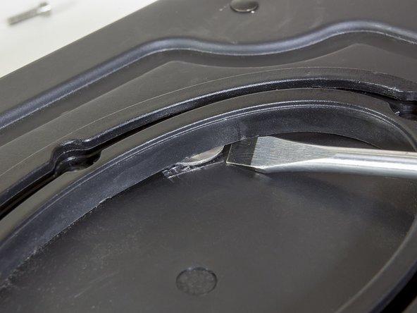 Mit dem Schraubendreher die ovale Schiene etwas anheben und die defekte Gewindeplatte durch die neue ersetzen. Beachte, dass die neue ovale Gewindeplatte wieder korrekt in die Führungsschiene eingebracht wird.