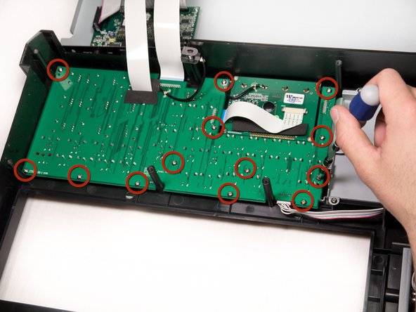 Using a Phillips #2 screwdriver, remove the thirteen 9.8 mm silver screws holding the mother board to the face plate.