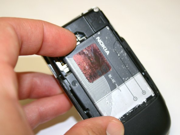 Use your index finger to first push down and then lift up the battery as shown.