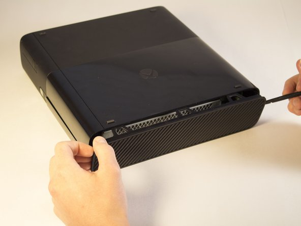 Continue sliding the spudger along the perimeter of the left grated face of the Xbox.