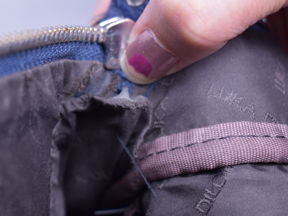 Tuck the zipper inside the flap of the backpack to cover the end of the zipper.