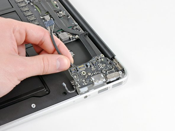 Carefully lift the I/O board from its edge nearest the logic board and remove it from the upper case.