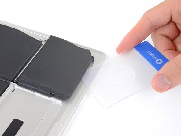 After 2-3 minutes, slide one corner of a plastic card underneath the battery cell.