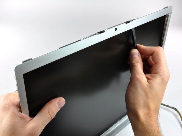 Work your way along the top edge of the LCD, slowly prying the attached steel strip away from the front bezel.
