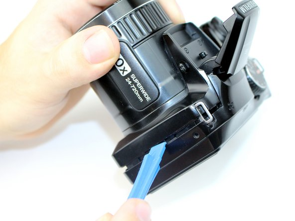 Use a plastic opening tool to separate the rear case from the camera on each of the sides until the panel is completely separated.