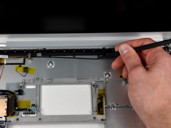 Carefully peel up the black adhesive tape securing the speaker cable along the rear edge of the lower case.