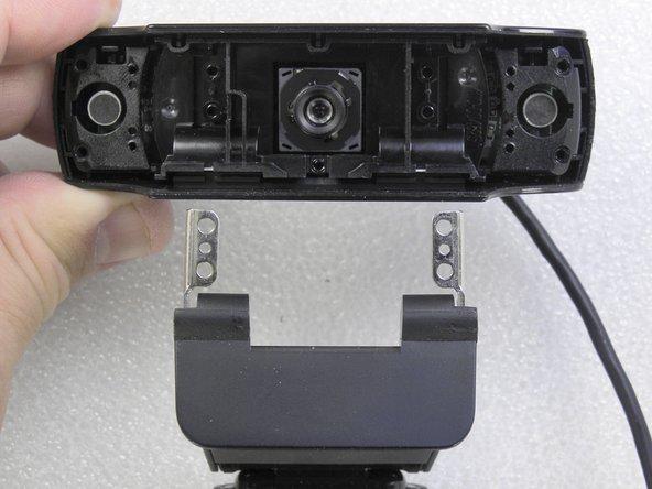 Cuidadosamente remova os suportes metálicos da base da webcam.
