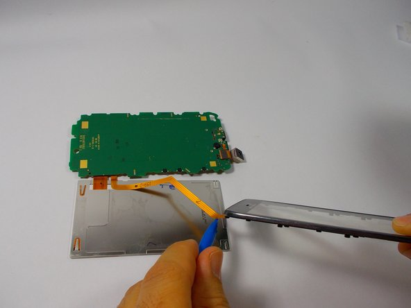 Remove the ribbon cable from the back of the lcd using the plastic opening tool or spudger.