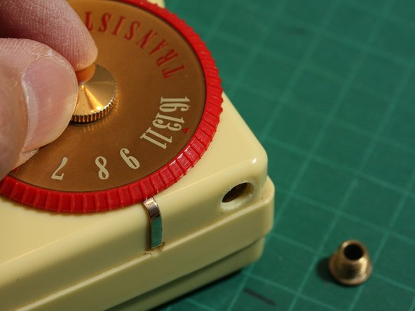Unscrew the large decorative screw in the center of the tuning dial by hand...