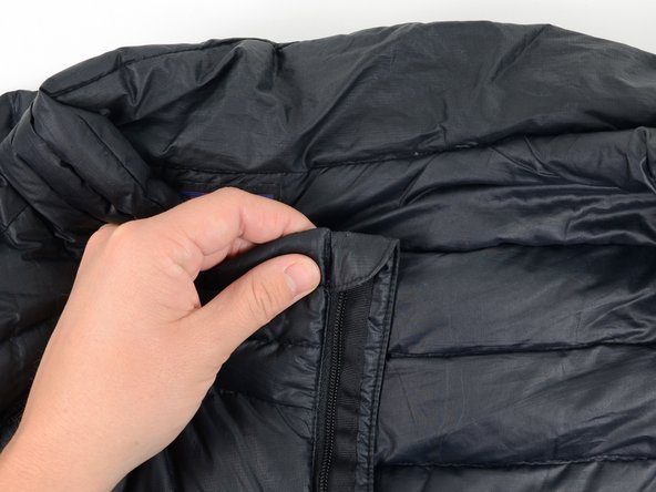 Locate the top of the zipper on the side with the slider.