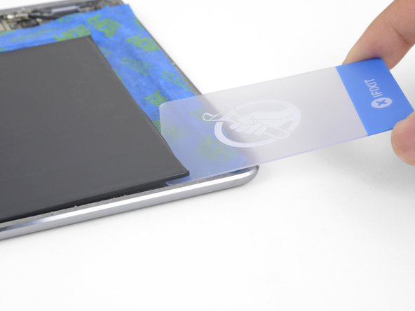 You can also approach the adhesive strip with the plastic card from battery's other bottom corner.