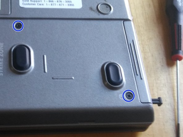 Now, remove the two drive screws, located in the bottom right of the laptop. These are helpfully labeled with a cylindrical hard drive icon.