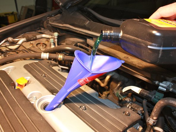 Using a funnel, pour 5 quarts of 5W-20 oil into the opening, making sure not to spill oil onto or around the engine.