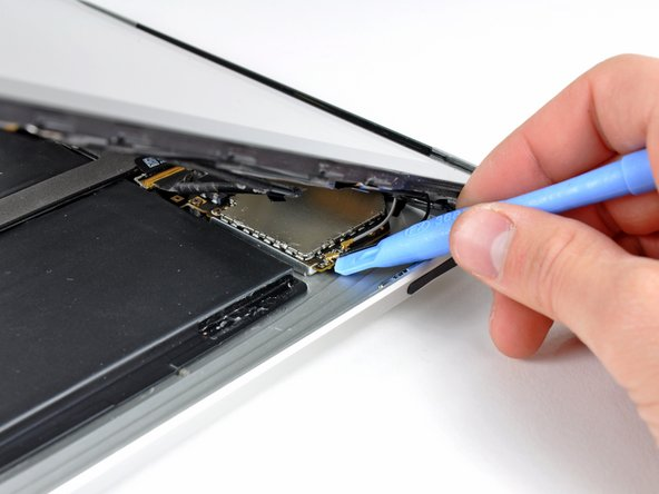 Use the flat end of a spudger to pry the antenna connector closest to the bottom of the iPad up off its socket on the communications board.