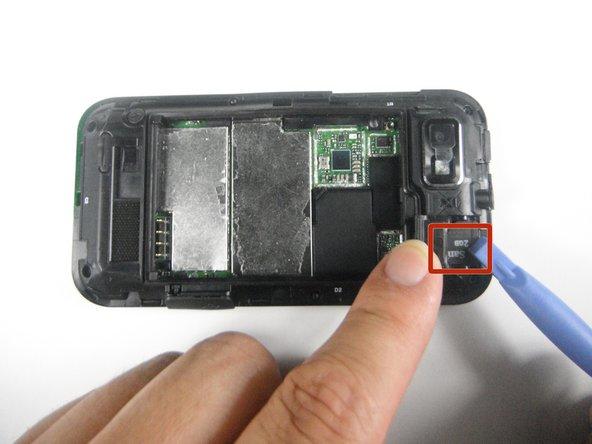 Locate the SD card beneath the plastic cover in the corner.
