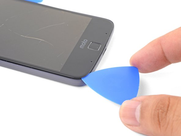 Insert an opening pick into a bottom corner and slice towards the home button, stopping before you reach it.