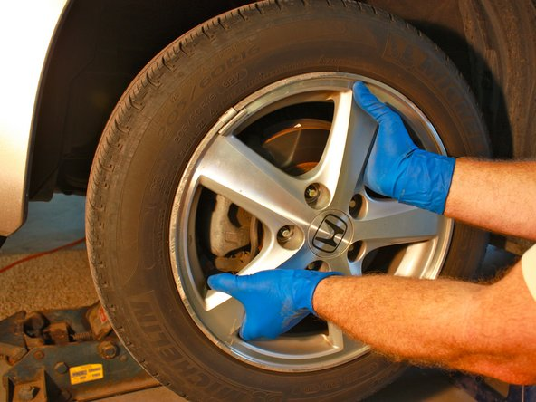 Remove the wheel and tire off the wheel studs, and place it aside.