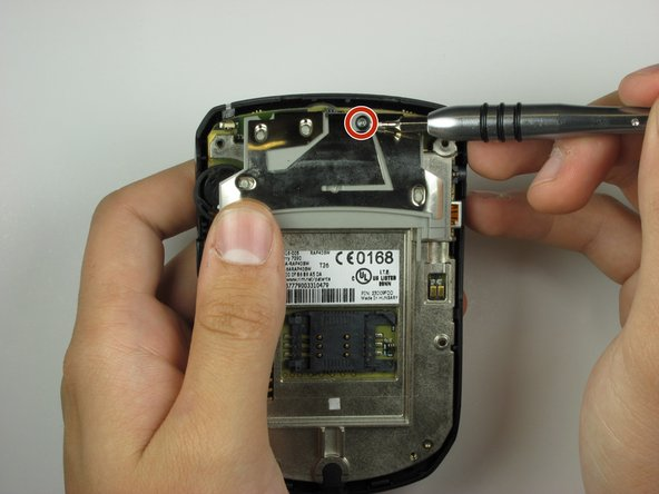Locate on the backside of the phone, a screw towards the top of the device.