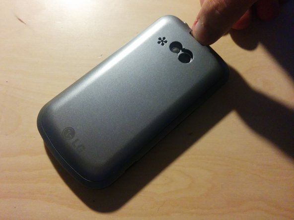 First, remove the backplate by pushing the button at the top of the back of the phone.