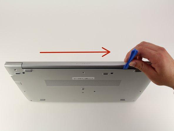 Stelle den Computer so, dass die Kante mit den Scharnieren nach oben zeigt.