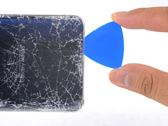 Slide the pick down the bottom edge of the phone.