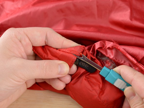 Insert the seam ripper between the two pieces of fabric and carefully rip any stitches between them that may hold the fabrics together.