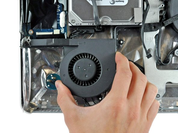 Pull the hard drive fan off the plastic posts protruding from the rear case and remove it from the iMac, minding any cables that may get caught.