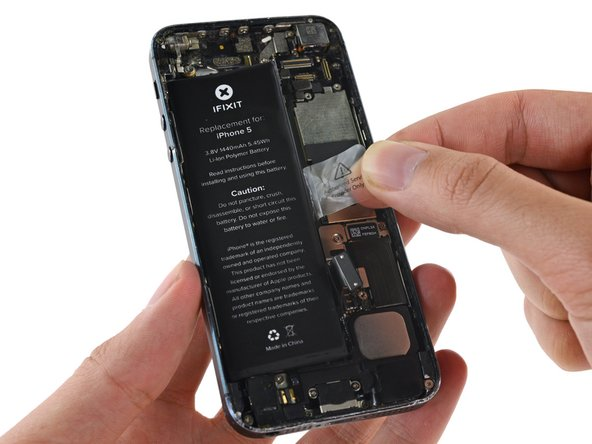 Use the exposed clear plastic pull tab to peel the battery off the adhesive securing it to the iPhone.